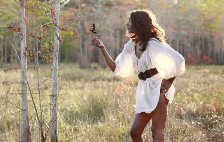 Sexy African American plays with a butterfly in the woods Banco de Imagens