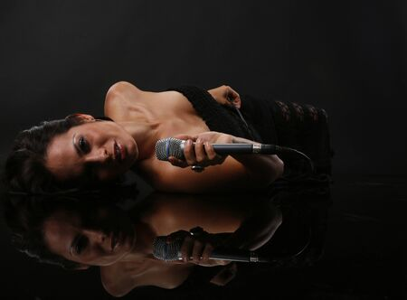 Young woman sings on a reflective floor Stock Photo - 18300116