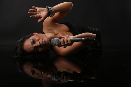 Young woman sings on a reflective floor Stock Photo - 18300124