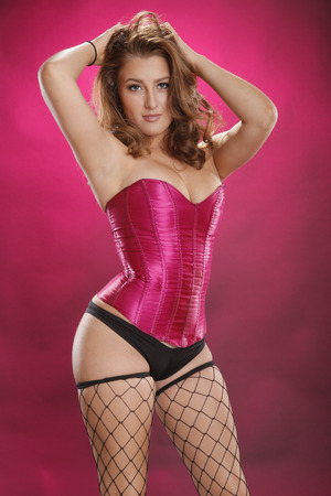 fishnet stockings: Gorgeous red-hair in sexy fishnet stockings on magenta Stock Photo