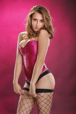 busty: Gorgeous red-pelo en medias de rejilla sexy en magenta Foto de archivo