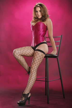 Gorgeous red-hair in sexy fishnet stockings on a stool  and magenta
