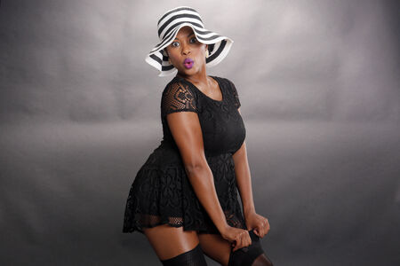 Expressions of a caribbean girl in lingerie with striped hat photo