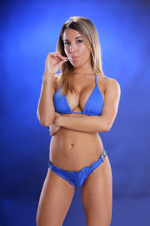 crave: Cute blond on blue backdrop and blue bikini chews away a lollypop