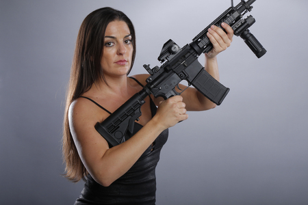 Gorgeous brunette in a little black dress and big gun