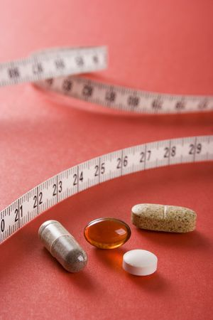 Pills and measure on the red backgraund (closeup)