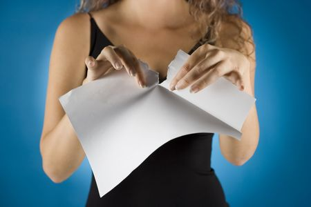 negate: woman tears white piece of paper Stock Photo