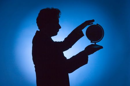 silhouette of man with globe on blue background photo
