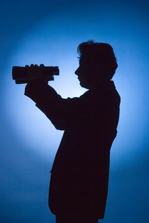 silhouette of man with binoculars on blue background photo