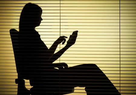 enumeration: silhouette of sitting woman with calculator over the blind Stock Photo