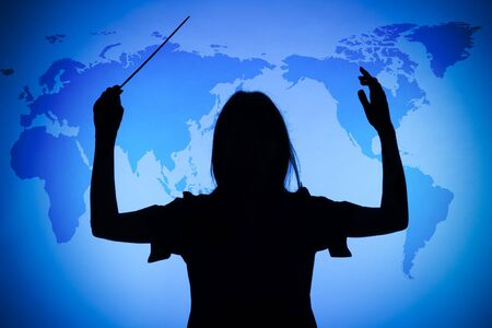 genie woman: silhouette of female conductor on the blue world map