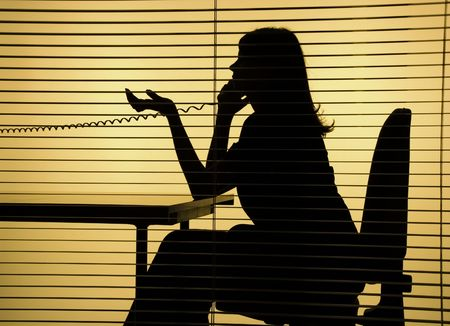 spy girl: silhouette of woman on the phone (view through the blind)