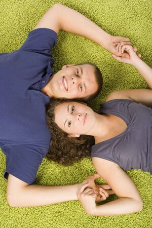 green carpet: young couple lying on the green carpet
