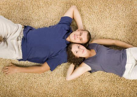 young couple lying on the beige carpet
