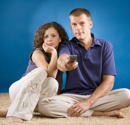 young couple on beige carpet with remote control photo