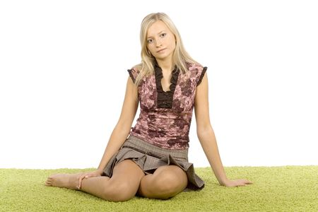 isolated on white young blonde woman sitting on the green carpet photo