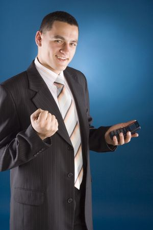 enumeration: happy businessman with calculator in his hand (blue background) Stock Photo