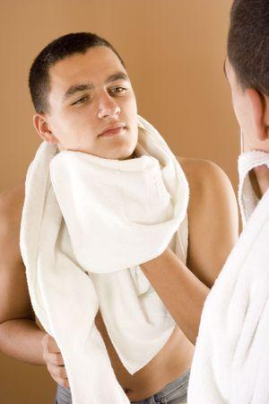 reflexion: reflexi�n del joven en el espejo del ba�o despu�s de afeitar