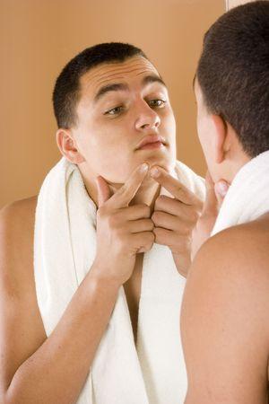 reflexion: reflexi�n del hombre joven en el espejo del cuarto de ba�o que limpia su piel