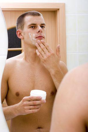 reflexion: reflexi�n del joven en el espejo del ba�o despu�s de afeitado