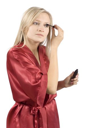 red bathrobe: young woman dressed red bathrobe putting mascara (pure white background) Stock Photo