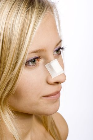 body wound: face of young woman with sticking plaster on nose (grey background) Stock Photo