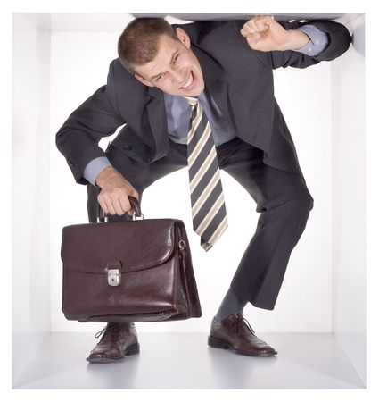 cramped: businessman with suitcase in the cramped white cube Stock Photo