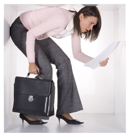 cramped: businesswoman with briefcase and papers in the cramped white cube  Stock Photo