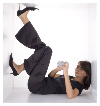 cramped: businesswoman with palmtopmobile phone in the cramped white cube Stock Photo