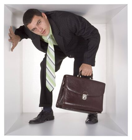 cramped: businessman with briefcase in the cramped white cube