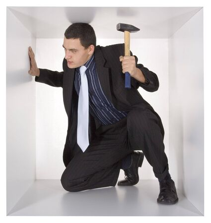 cramped: businessman with hammer in the cramped white cube