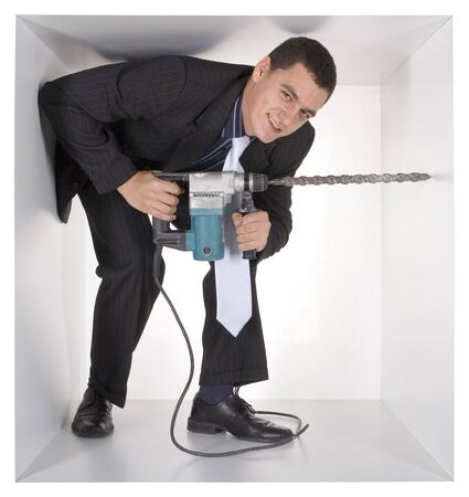 cramped: businessman with drill in the cramped white cube