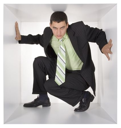 cramped: businessman in the cramped white cube Stock Photo