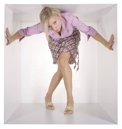 cramped: blonde businesswoman in the white cube Stock Photo