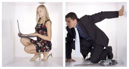 cramped: agent watching blonde businesswoman throw whole in the cube Stock Photo