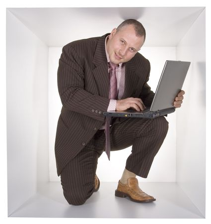 cramped: businessman with laptop in the cramped white cube