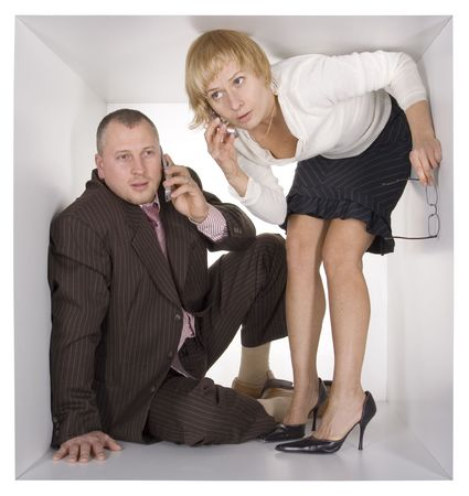 cramped: businesspeople in the small white cube - mobiles Stock Photo