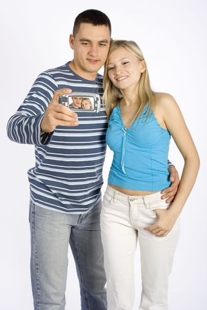 communicaton: young man and woman taking picture by phonepalmtop