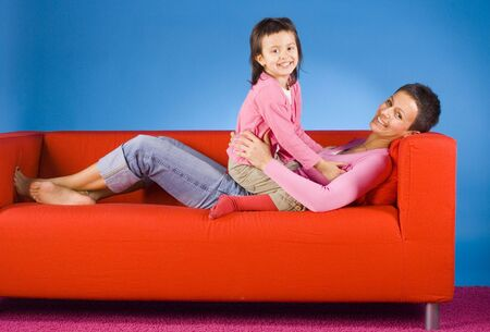 red sofa: woman and her daughter on the red sofa Stock Photo