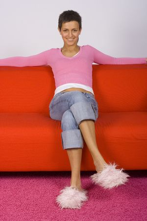 restfulness: woman sitting comfortable on the red sofa, looks happy