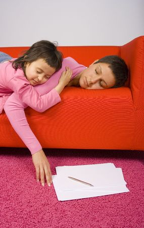 woman and her daughter sleeping on the red sofa - papers on the floor