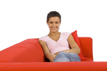 restfulness: beautiful woman lying on the red sofa