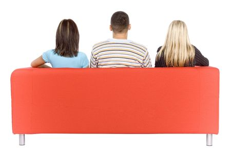 Back of man and two women sitting on a red couch.  Isolated on white background, in studio. photo