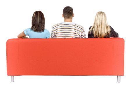 mann couch: Zur�ck von Mann und zwei Frauen sitzen auf einer roten Couch. Isoliert auf wei�em Hintergrund, im Studio.