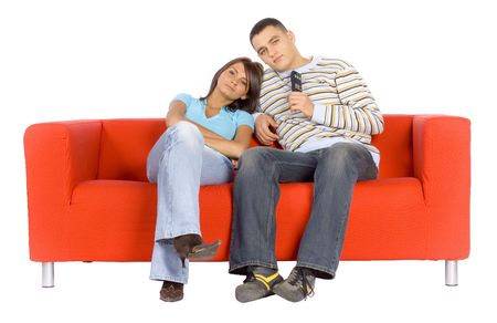 red couch: Man and woman sitting on a red couch with remote control.  Isolated on white background, in studio.