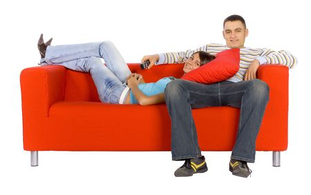 Man and woman sitting on a red couch with remote control.  Isolated on white background, in studio.