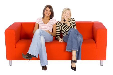 Two women sitting on a red couch with remote control.  Isolated on white background, in studio. Stock Photo - 757023