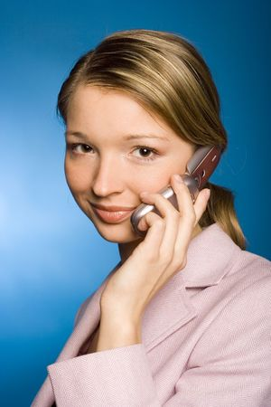 Young woman with mobile phone, blue background in studio Stock Photo - 756988