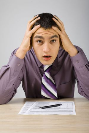 repayment: Shocked man at the desk. Theres some papers on the desk and a pen. (papers form is copyright free)