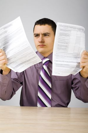 repayment: Angry man at the desk holding (crumple) two sheets of paper. (papers form is copyright free) Stock Photo